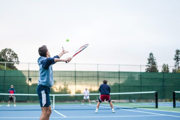 four men playing double tennis during daytime